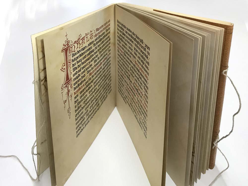 Blick in Buchseiten, Text schwarz, Initialien rot