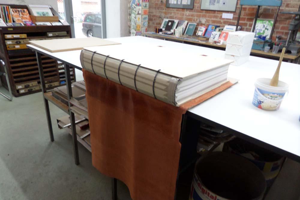 Leder wird mit Kleister um den Buchblock geklebt