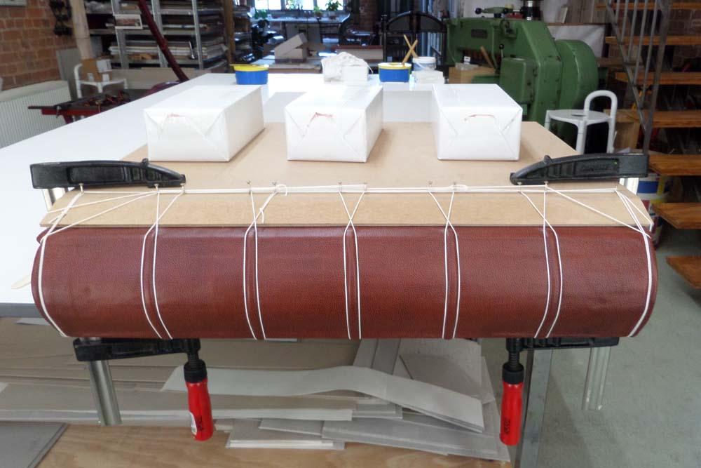 Buch zwischen Brettern eingepreßt, die erhabenen Bünde beim Trocknen mit Kordel abgebunden